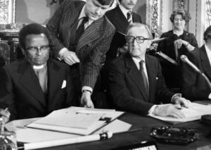 Bishop Abel Muzorewa signs the Lancaster House Agreement seated next to British Foreign Secretary Lord Carrington