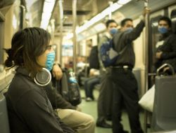 People in Mexico City wear masks on a train